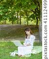 年輕女性模型坐草坪做著這台膝上型計算機 41112499