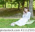 年輕女性模型坐草坪和談話 41112503
