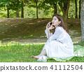 年輕女性模型坐草坪和談話由手機 41112504