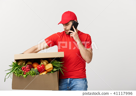 Delivery man holding paper box with food and making a call with mobile phone isolated over grey 41117996