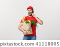 Handsome grocery delivery man talking to mobile and holding grocery paper bag. 41118005
