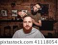 Barber and bearded man in barber shop 41118054