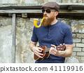 Man with beard playing ukulele and smoking a pipe 41119916