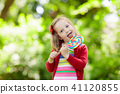 Little girl with colorful candy lollipop 41120855