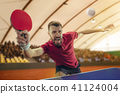 The table tennis player serving 41124004
