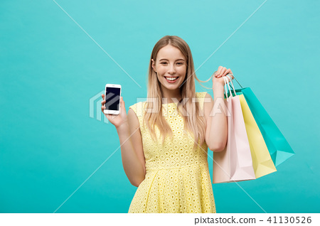 Portrait young attractive woman with shopping bags shows the phone's screen directly to the camera 41130526