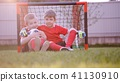 Little soccer players are sitting at the soccer goal on the lawn 41130910