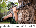 Private millitary holding gun aiming behind a tree 41135071