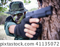 Private millitary holding gun aiming behind a tree 41135072