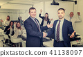 businessmen shaking hands while finishing up meeting 41138097