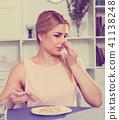 Sporty girl is feeling disgust when breakfast with oatmeal porridge 41138248