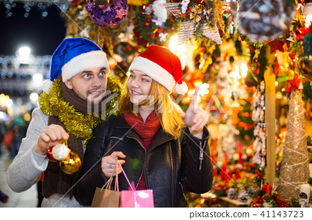 Girl with boy in Christmas hat choosing decorations 41143723