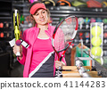 smiling sporty woman in uniform is holding new racket for padel and tennis in the store 41144283