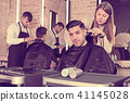 Hairdresser doing styling of guy with electric hair clipper 41145028