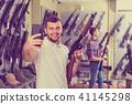 Male customer is taking selfie on phone with air gun 41145298