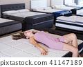 Smiling woman testing a modern mattress 41147189