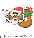 Santa with gift bundt cake mascot cartoon 41150923