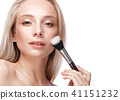 Beautiful young girl with a light natural make-up, brushes for cosmetics and nude manicure. Beauty 41151232