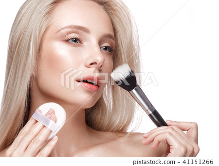 Beautiful young girl with a light natural make-up, brushes for cosmetics and nude manicure. Beauty 41151266
