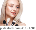Beautiful young girl with a light natural make-up, brushes for cosmetics and nude manicure. Beauty 41151281