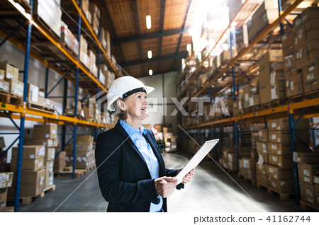 Senior woman warehouse manager or supervisor with tablet, working. 41162744