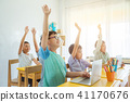 children rising hand up with smile in classroom 41170676