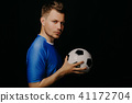 Close-up portrait of young handsome football player soccer posing on dark background. 41172704