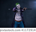 Grim evil character with drawings on the body keeps the stick. green hair 41172914