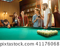 Young men and women playing billiards at office after work. 41176068