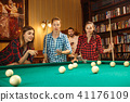 Young men and women playing billiards at office after work. 41176109
