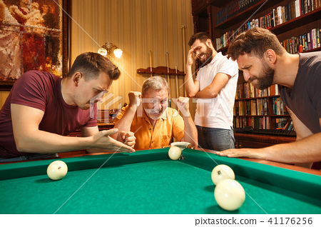 The displeased men playing billiards at office after work. 41176256