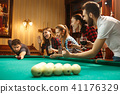 Young men and women playing billiards at office after work. 41176329