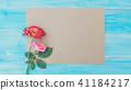 Red and pink rose on a brown paper and blue wooden 41184217