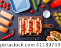 Picture on top of buns with sausages on cutting board, on table with cucumbers 41189749