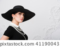 Portrait of a beautiful young woman in retro style in an elegant black hat and dress over luxury 41190043