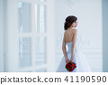 Fashion photo of a beautiful bride with flowers bouquet in her hands at the light room next to the 41190590