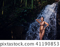 Beautiful young girl is washed in a tropical shower, happy, smiling. Concept of heat summer during 41190853
