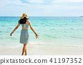 Woman walking towards the sea water 41197352