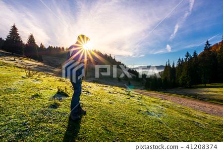 photographer in sunburst shooting foggy landscape 41208374