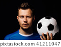 Close-up portrait of young handsome football player soccer posing on dark background. 41211047