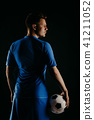 Young soccer player with ball on black background in studio. 41211052