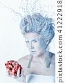 Snow queen with unusual makeup and heart in hands 41222918