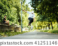 boy performs a trick on a skateboard while the girl sits and watches 41251146