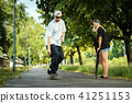 man with a skateboard shows a woman how to ride 41251153