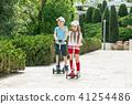 Preschooler girl and boy riding scooter outdoors. 41254486