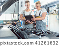 Experienced auto mechanic using a laptop for scanning engine errors 41261632