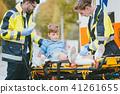 Medics putting injured boy on stretcher after accident 41261655