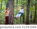 Woman watches man doing exercises on high bars 41261666