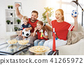 family of fans watching a football match on TV at home 41265972
