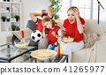 family of fans watching a football match on TV at home 41265977